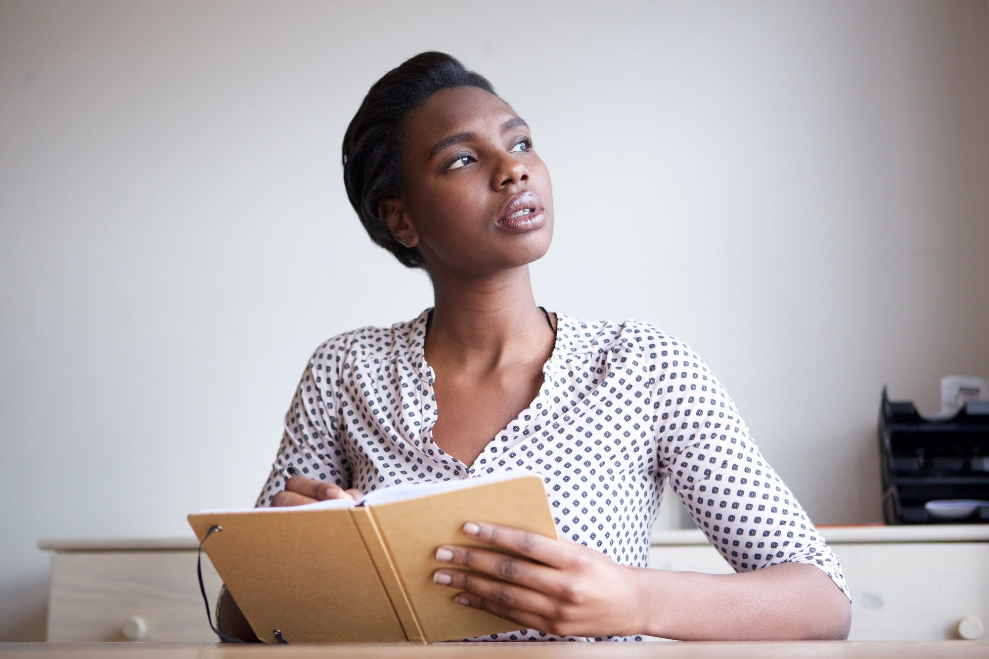 serious young woman thinking and writing in journal